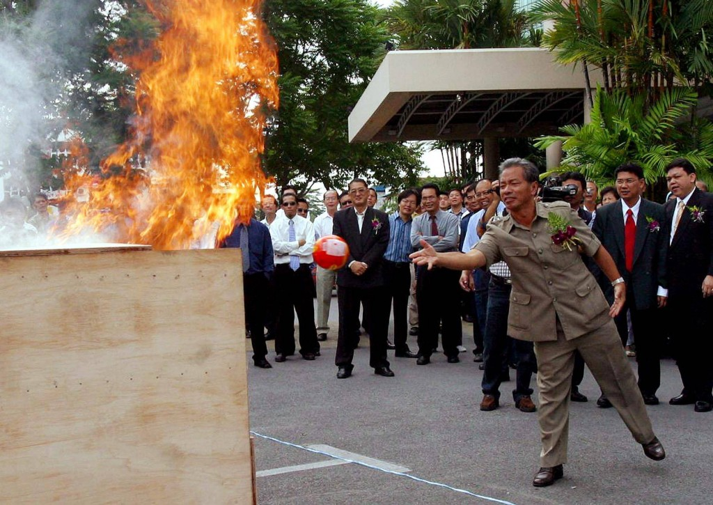 A fire suppression ball is being tossed into the fire during a demonstration in Kuching, Sarawak.