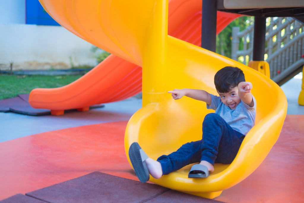 Asian kid playing slide at the playground under the sunlight in