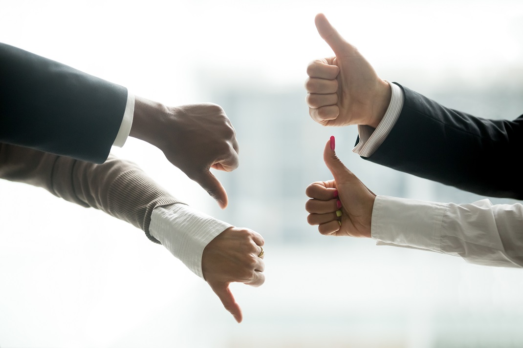 Hands of diverse business people showing thumbs up and down