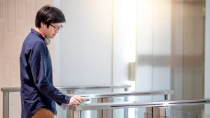 Young Asian business man using smartphone to open automatic gate