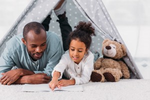 african american father and daughter reading book together at home