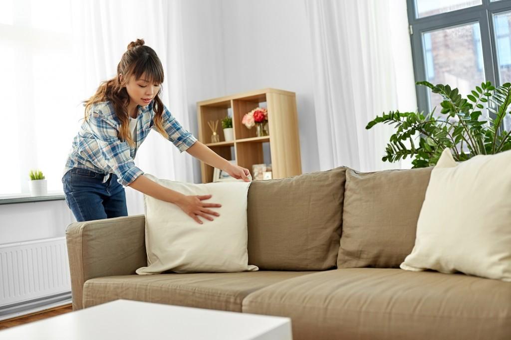 asian woman arranging sofa cushions at home