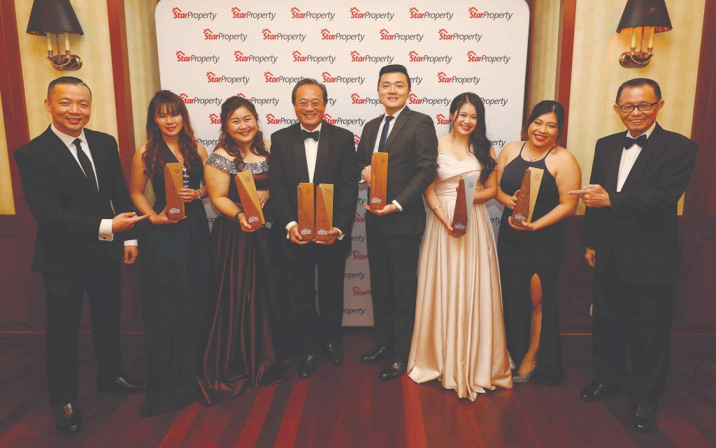 Celebrating their big win, OSK property development chief operating officer Seth Lim Sow Wu (4th from left) takes a group photo with his team holding up their seven trophies as Fu (right) and Yap (left) point to their big haul.