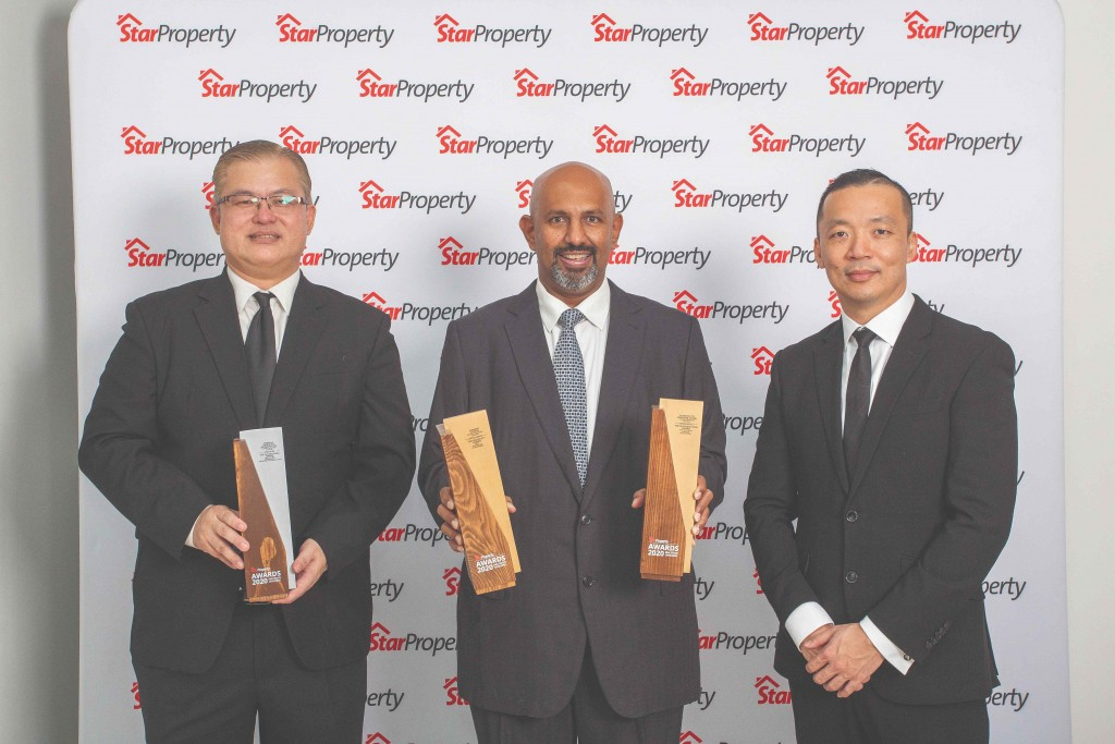 Sunway City Iskandar Puteri CEO Gerard Soosay (centre) and assistant general manager Ng Chai Teck (left) hold up their trophies as Yap looks on.