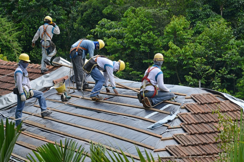 20658398 - workers doing installation work on the roof of a building