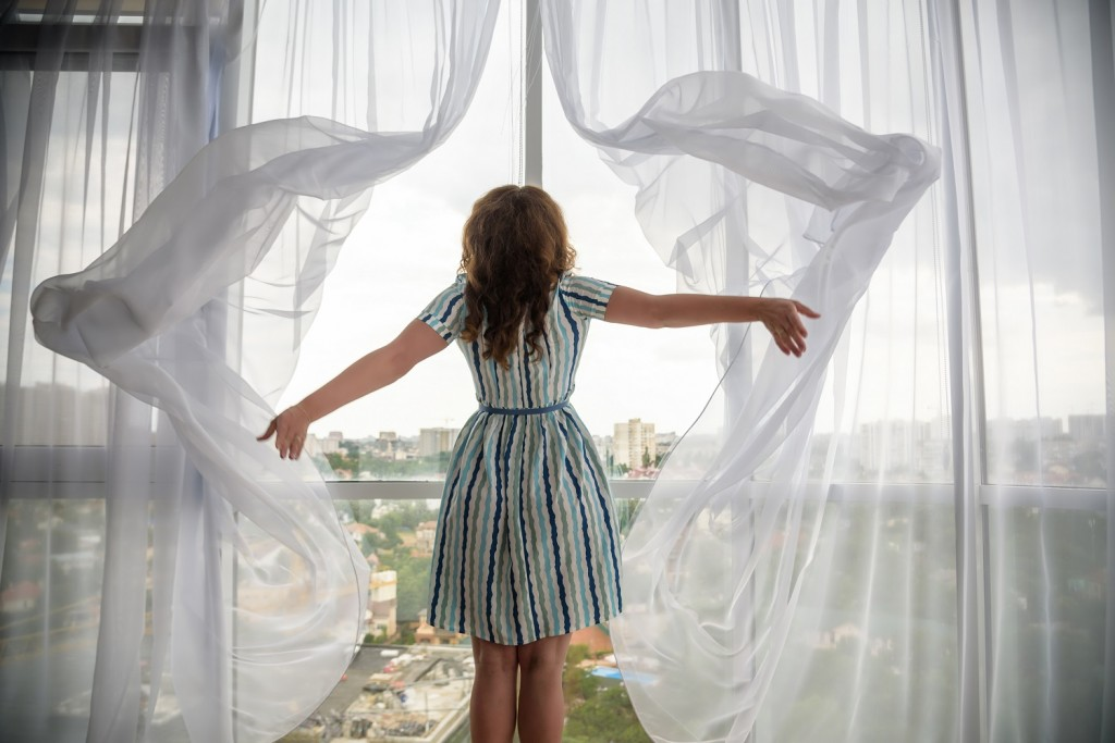 Rear view of a young joyful woman wearing fashion dress and holding the curtains open to look out of large light window at home, turning to look and smile at camera, interior