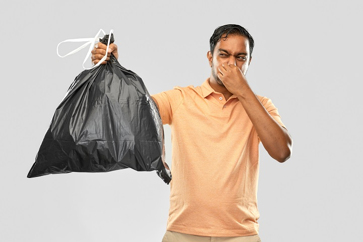 indian man holding stinky trash bag