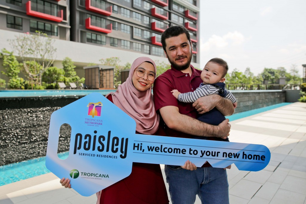 Owners Islom and Miza, with their baby, receive the mock key to their unit.