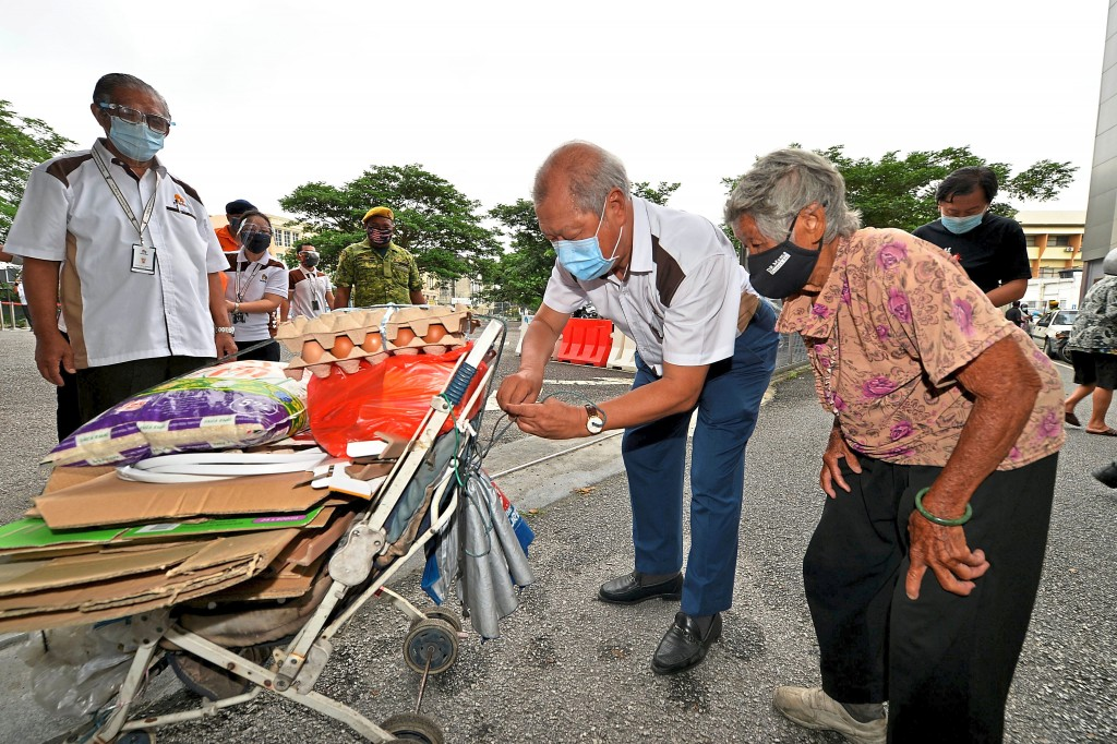 Matrix Concepts founder Datuk Lee Tian Hock assisting an 89-year-old woman to secure the donated  food items to her trolley.